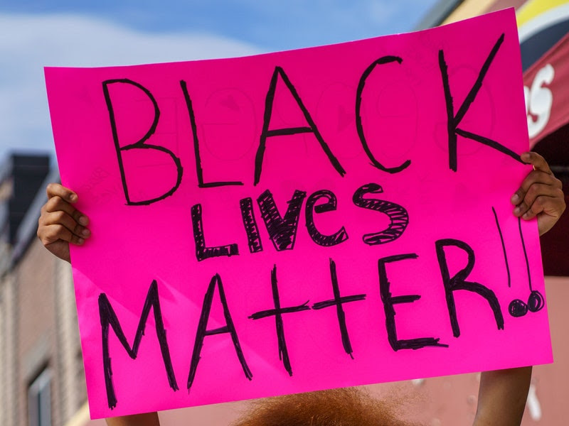 Image of a Black protester holding a pink sign reading in handwritten black lettering %22BLACK LIVES MATTER!!%22 at a street protest
