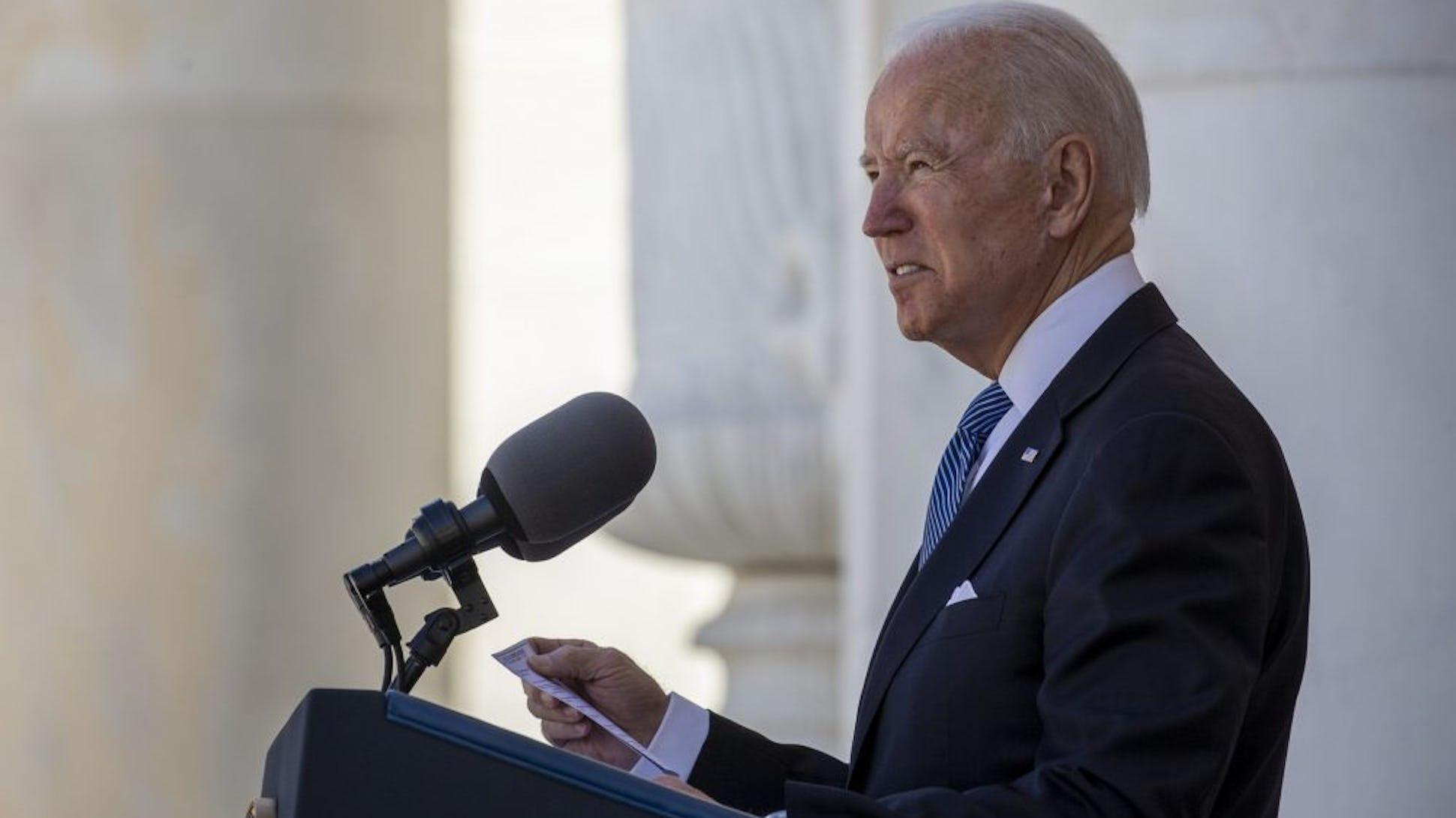 President Joe Biden stands behind a podium, giving a speech