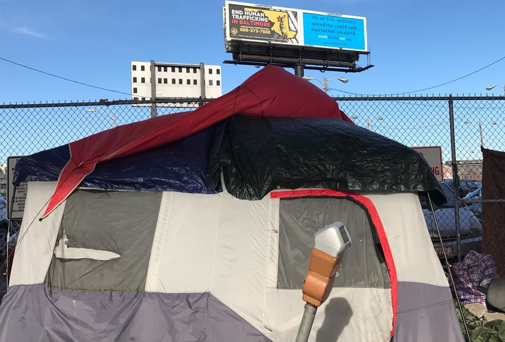 "Homeless encampment in the foreground of a Baltimore, MD billboard that read, ""3% of US military spending could end starvation on earth."" Source World Beyond War."