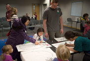 Children make pillowcases for emergency supplies at the Spokane Public Library's South Hill branch. (Photo by Tyler Tjomsland /The Spokesman-Review)