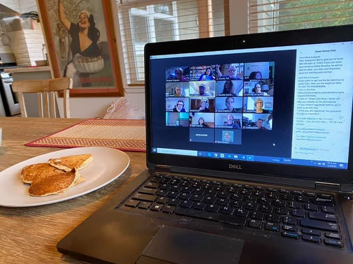 A laptop on a kitchen table, showing a virtual meeting for the phonebank event.