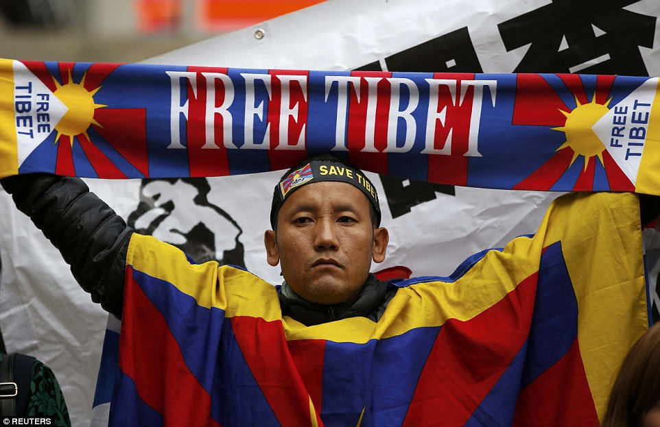 Rival group: A pro-Tibet protester wears a Tibetan flag and carries a 'free Tibet' scarf as he stands alongside pro-China demonstrators