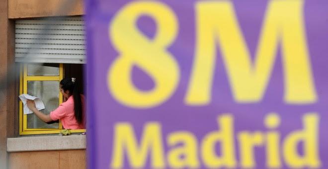 Una mujer limpia una ventana junto a un cartel alusivo al Día Internacional de la Mujer, este viernes en Madrid. EFE/Chema Moya