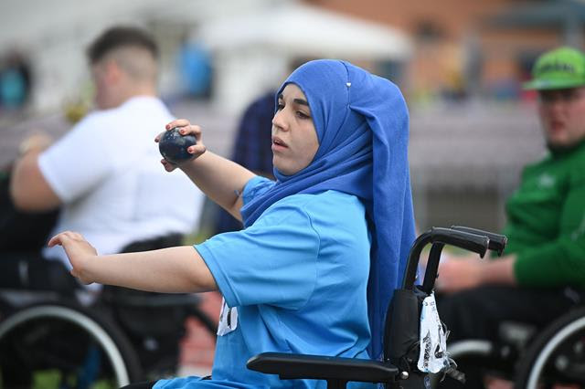 A young woman in her wheelchair throwing a shot put