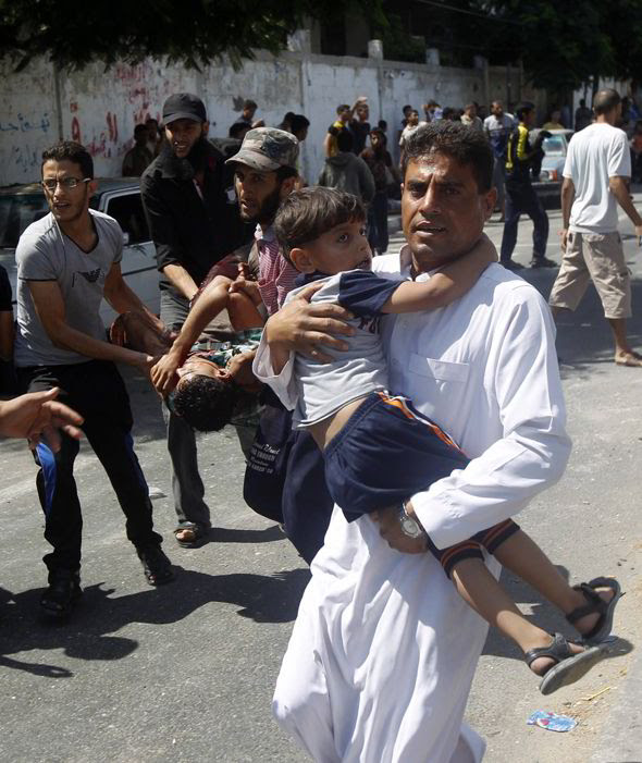Palestinians carry injured people following an Israeli military strike on a UN school in Rafah, in the southern Gaza Strip on August 3, 2014. At least 10 people were killed in a fresh strike on a UN school in southern Gaza which was sheltering Palestinians displaced by an Israeli military offensive, medics said.  [AP]