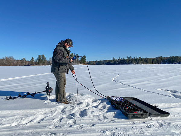 A Michigan Department of Natural Resources fisheries technician is shown lowering a probe to measure dissolved oxygen.