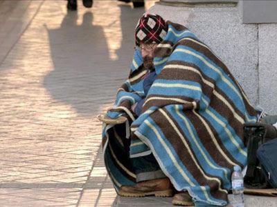 Una persona sin hogar se protege con una manta del frío en una calle de Madrid.