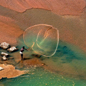 This stunning image shows a Santhal fisherman in West Bengal, India, casting his net.