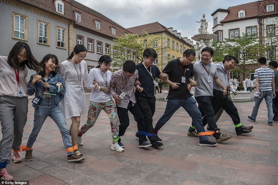Huawei workers play a team-building game at the end of their lunch break at the office complex
