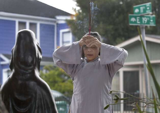 Vina Vo prays before a statue at the shrine, which has become an informal site for Buddhist ceremonies. Photo: Paul Chinn, The Chronicle