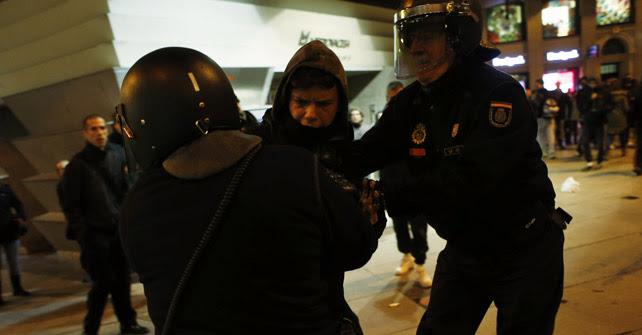 Dos agentes antidisturbios agarran a un manifestante en apoyo a Gamonal en la Plaza de Callao de Madrid.