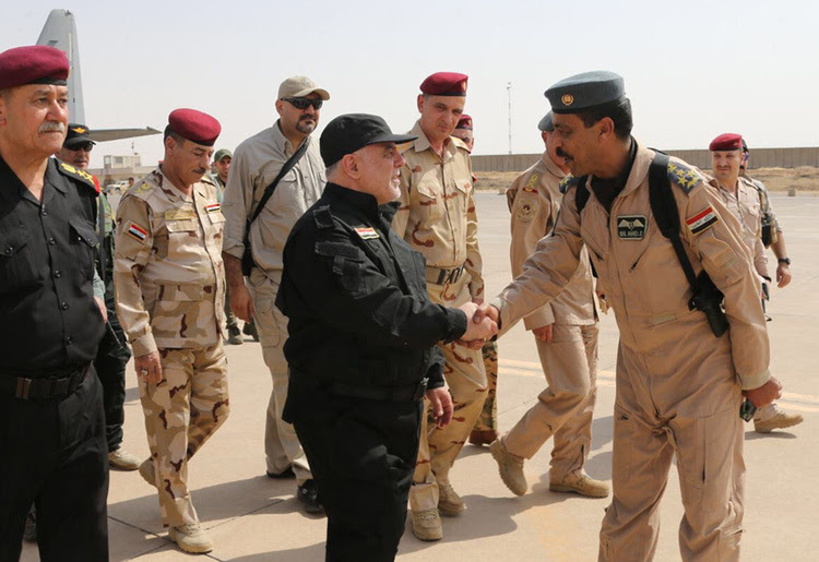 Iraqi Prime Minister Haider al-Abadigreets army officers in Mosul. (Iraqi Prime Minister's Office/HO/AFP)