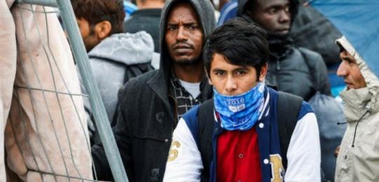Des migrants patientent devant le centre Porte de La Chapelle, à Paris.(G. Van Der Hasselt/AFP)