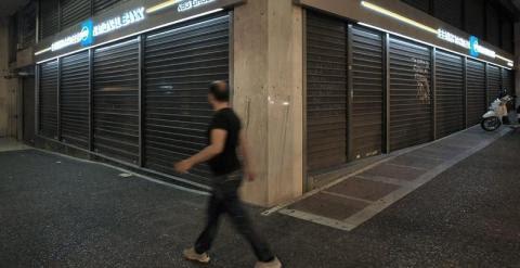 Un hombre camina delante de una sucursal cerrada del banco nacional de Grecia en Atenas./ EFE