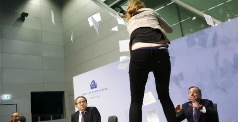 Una joven se sube a la mesa donde estaba Mario Draghi. /REUTERS