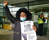 Cymru-Wales UNISON member Kemba Hadaway-Morgan protesting for Black Lives Matter, with a poster and her fist raised