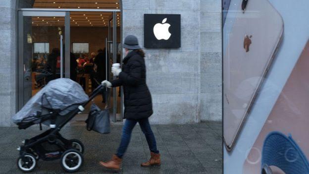 mulher passando na frente da Apple