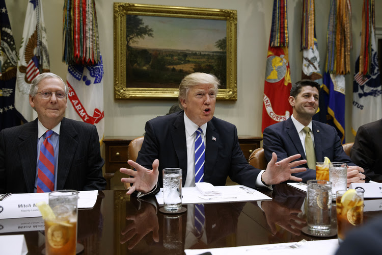 President Trump, flanked by Senate Majority Leader Mitch McConnell and House Speaker Paul Ryan, speaks in the Roosevelt Room in March. (Evan Vucci/AP)