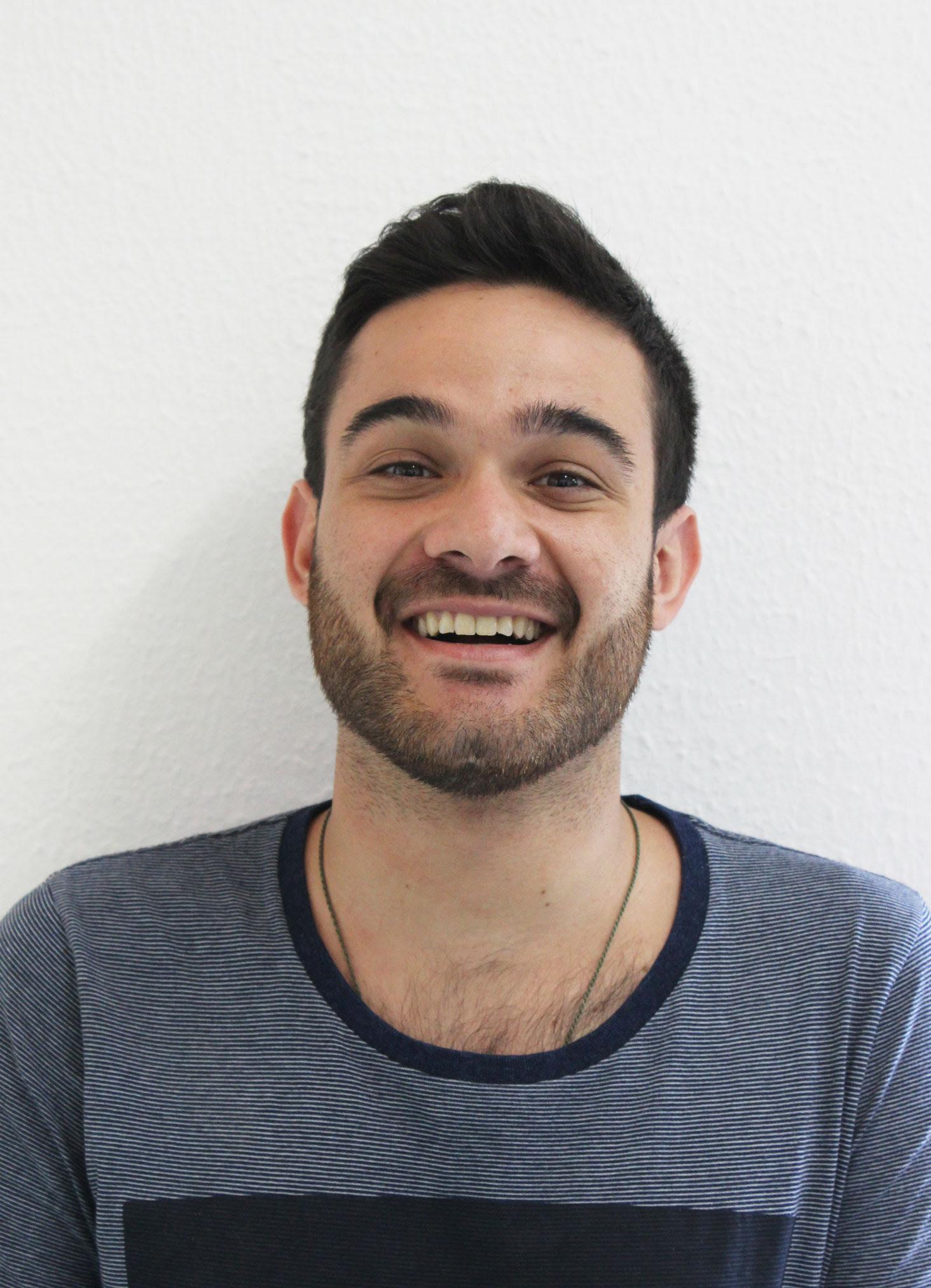 DESCRIÇÃO DA FOTO 3x4: Matheus tem pele branca, cabelo curto, preto, e barba rala. Ele está com um sorriso largo, olhos fechados e veste uma camiseta azul escuro.