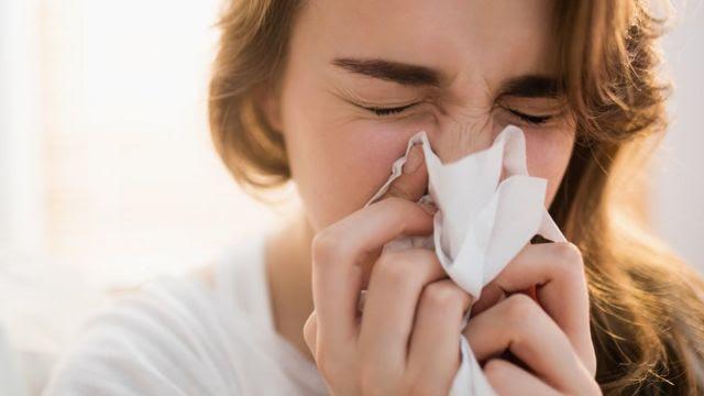 Una mujer se suena la nariz