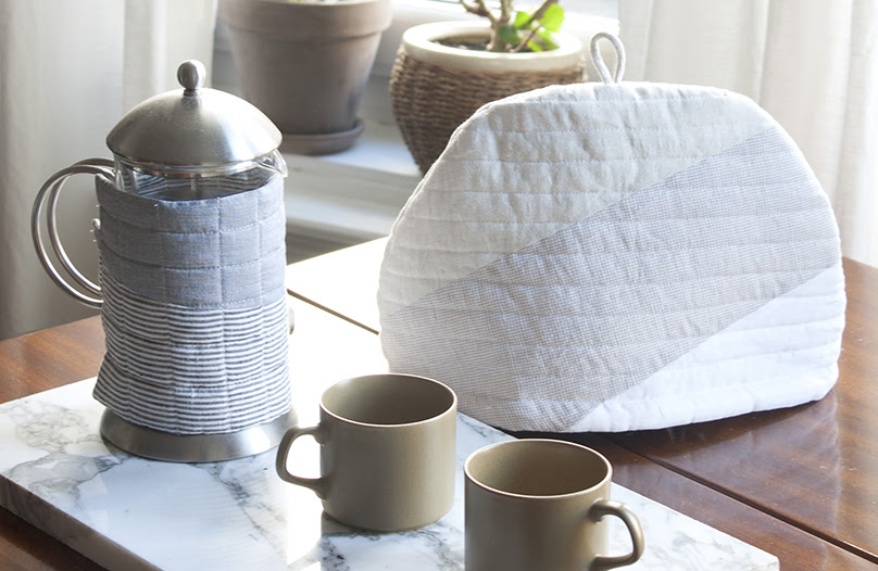 A photograph of a tea and coffee set on a wooden table, by a window. On the foreground there is a french press and two beige mug on a marble plate, the french press is wrapped in a quilt warmer by Woolgathering. Behind, there is a teapot covered by a quilt warmer by Woolgathering. There is plenty of sunlight and plants at the window.