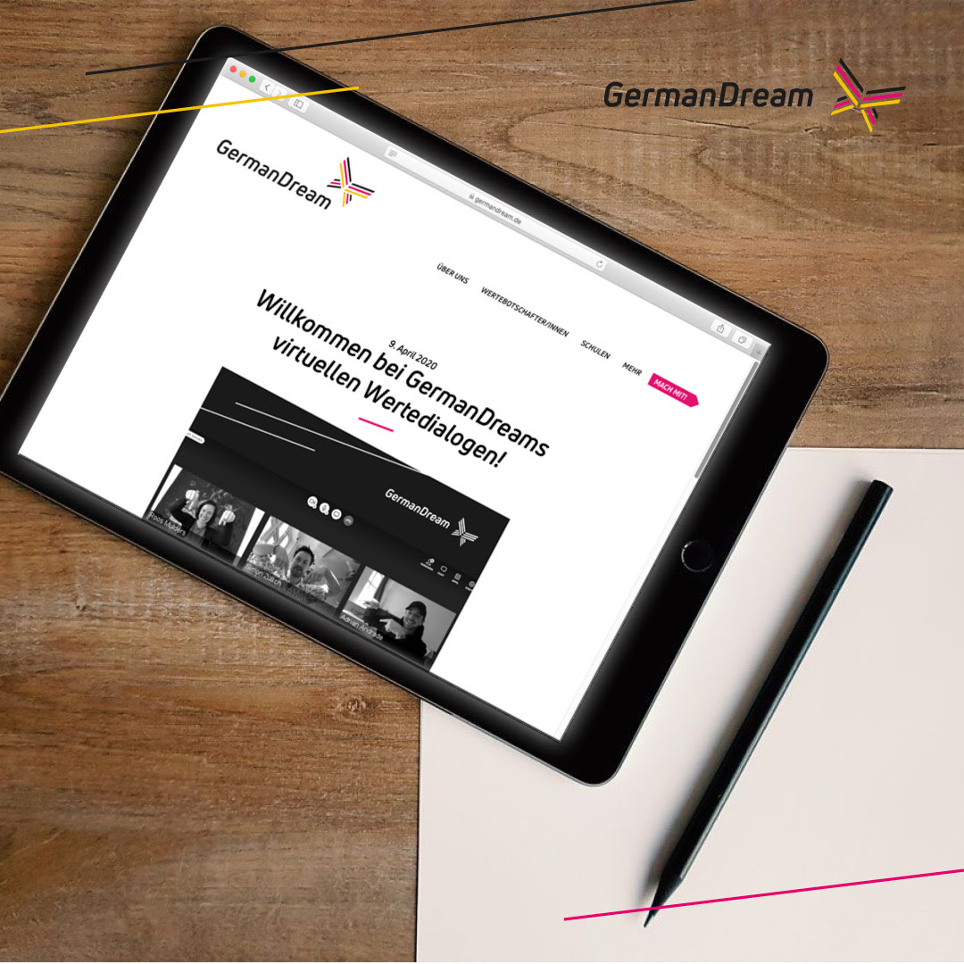 Tablet, auf dem die German Dream-Webseite aufgerufen ist, nebst Stift und Papier auf einem Holztisch