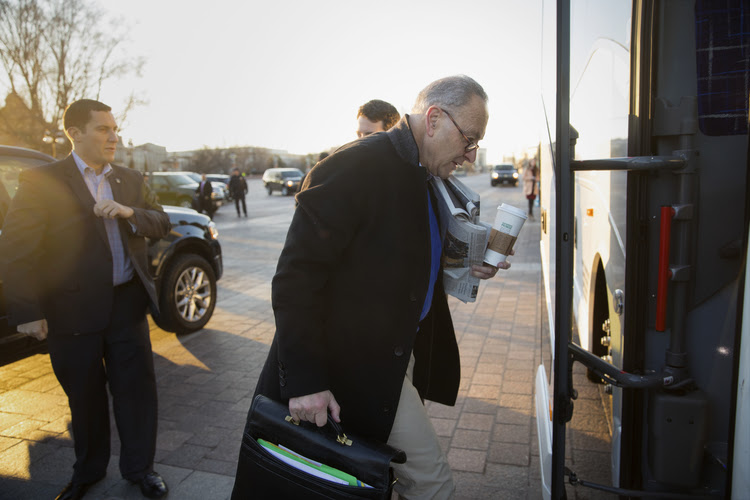 Chuck Schumer boards a bus at the Capitol to a Democratic retreat. (J. Scott Applewhite/AP)</p>
