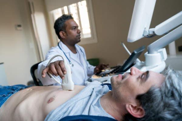 Doctor haciendo una ecografía del corazón a un paciente masculino de mediana edad