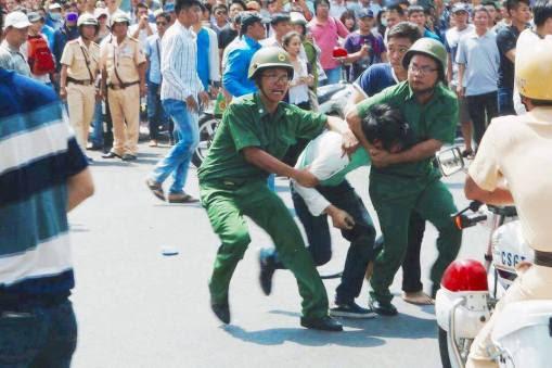 Các nhân viên mặc sắc phục kẹp cổ một biểu tình viên. Nguồn: internet