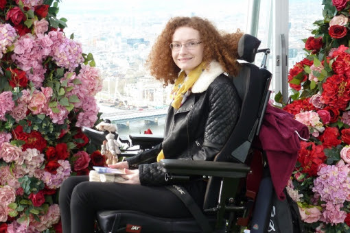 Hannah Deakin with red curly hair in her wheelchair wearing black trousers and a black leather jacket in front of an archway of pink and red flowers