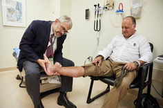 A doctor examines a man's ankle.