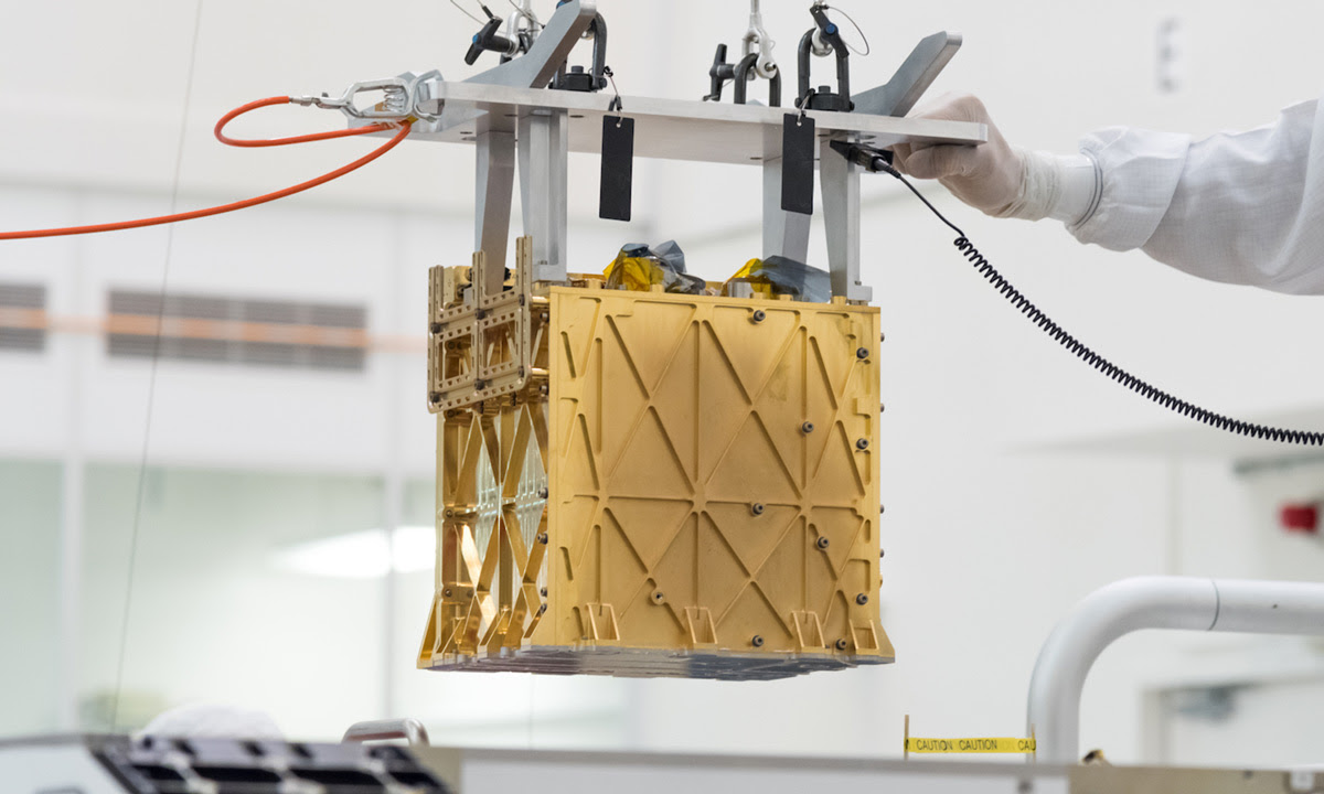 The MOXIE instrument is lowered into the rover in the clean room.