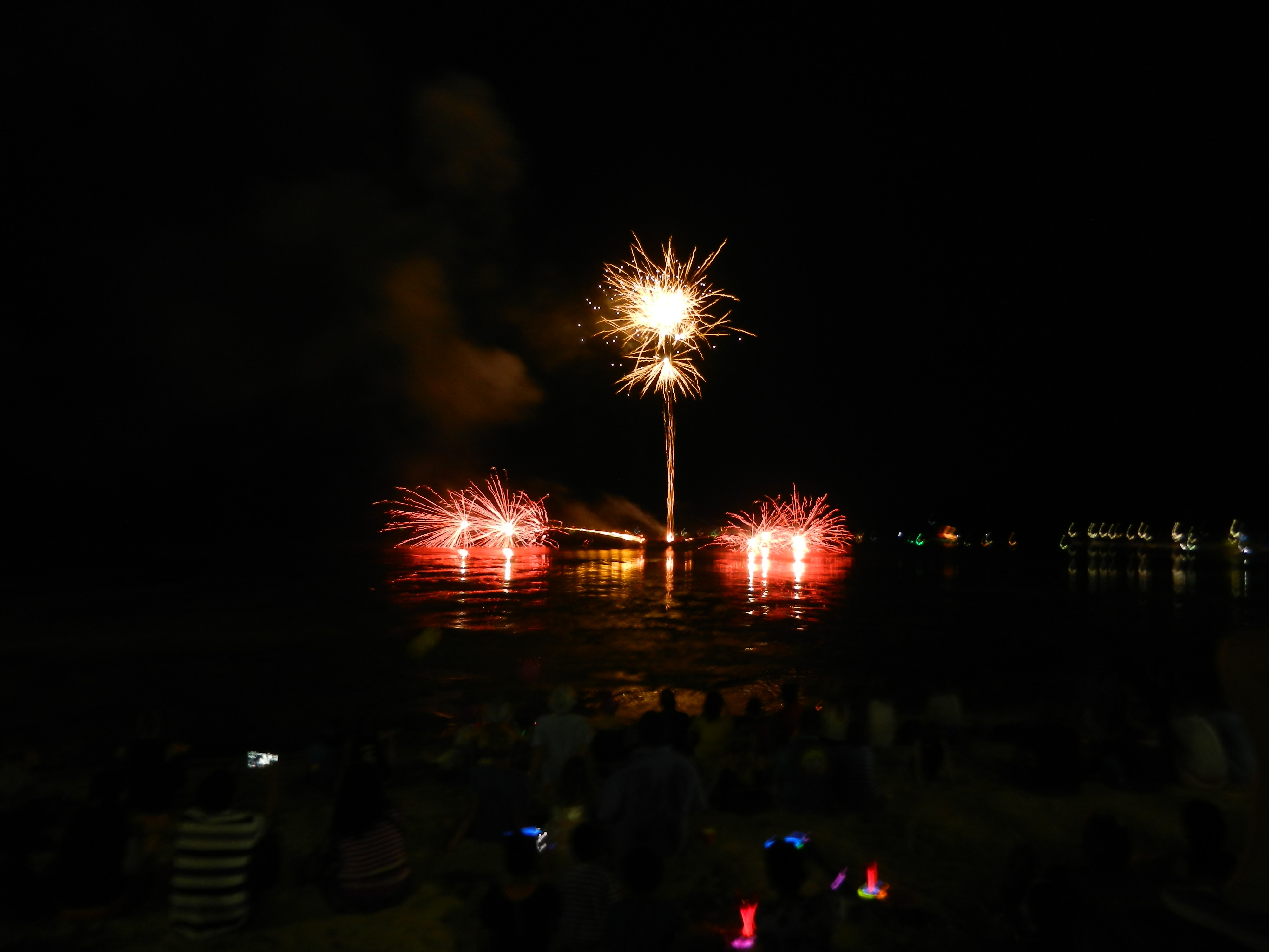 Two red fireworks lower on the horizon with one yellow firework high above.