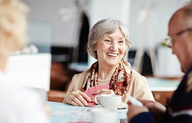 A smiling senior woman drinking coffee and playing cards with a friend.