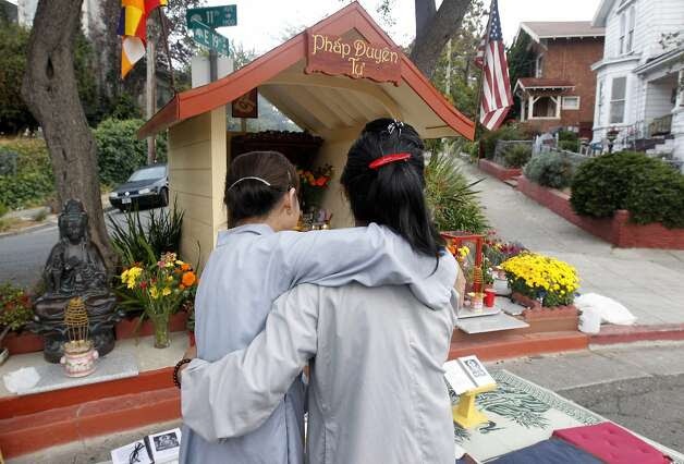 Lien Huynh (left) and Kieu Do embrace before a prayer session at sunrise in front of a Buddhist altar erected at 11th Avenue and East 19th Street in Oakland, Calif. on Saturday, Sept. 13, 2014. Photo: Paul Chinn, The Chronicle