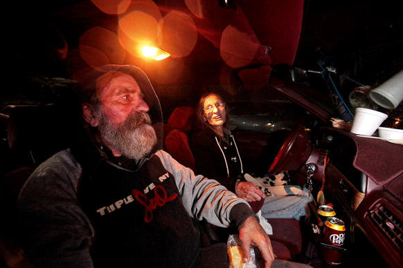 """Siblings Addison Dorsten, 59, left, and Christine Chapman, 65, right, eat dinner in their car at the Sonoma County """"Safe Parking"""" lot at the fairgrounds in Santa Rosa."""