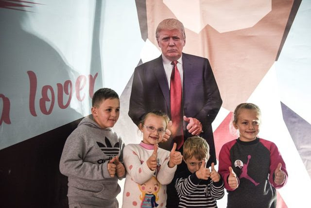 Children pose next to a cardboard depicting the US President Donald Trump  near the town of Ferizaj on January 28, 2017, at a restaurant where  45 pizzas were given for free in honor to the new elected  President of the United States of America. / AFP / Armend NIMANI        (Photo credit should read ARMEND NIMANI/AFP/Getty Images)