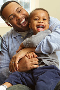 Smiling dad hugging laughing son
