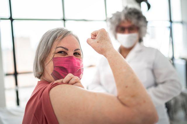 Mujer que está vacunada y flexionando el músculo del bíceps