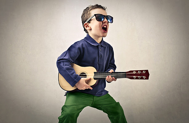 A little boy singing and playing the guitar with sunglasses on.