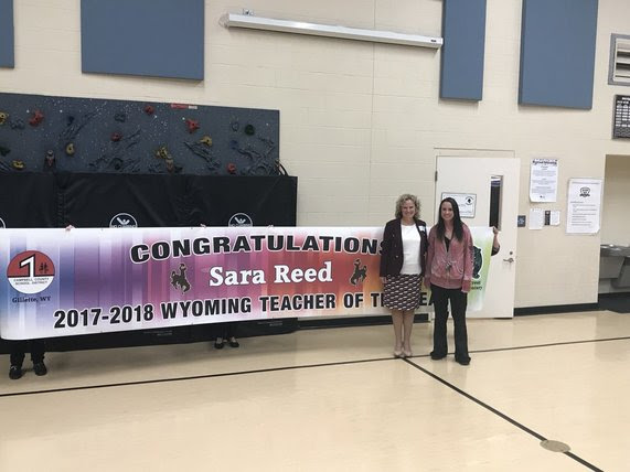 "State Superintendent Jillian Balow and Sara Reed stand in front of a large banner that reads, ""Congratulations Sara Reed, 2017-2018 Wyoming Teacher of the Year"""