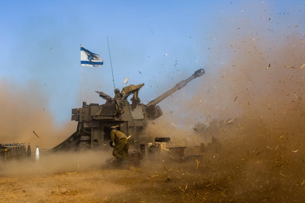 Israeli soldiers use a self-propelled howitzer fire a shell towards Gaza at a position in Southern Israel.