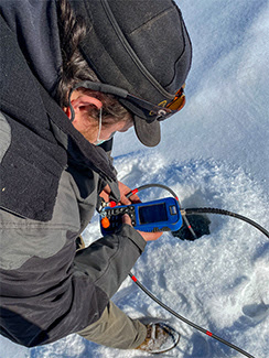 A DNR staffer measures the dissolved oxygen at an Upper Peninsula lake.