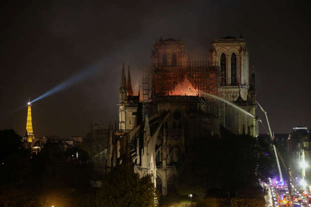 Slide 5 of 31: Firefighters douse flames billowing from the roof at Notre-Dame Cathedral in Paris on April 15, 2019. - A colossal fire swept through the famed Notre-Dame Cathedral in central Paris causing the spire to collapse and raising fears over the future of the nearly millenium old building and its precious artworks. The fire, which began in the early evening, sent flames and huge clouds of grey smoke billowing into the Paris sky as stunned Parisians and tourists watched on in sheer horror. (Photo by ludovic MARIN / AFP)        (Photo credit should read LUDOVIC MARIN/AFP/Getty Images)