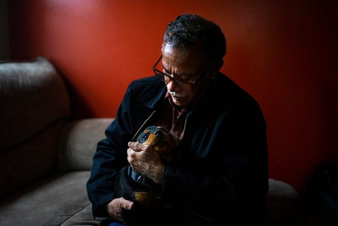 Lester Earley plays with his Rottweiler puppy inside his home in Detroit on April 8, 2021. Earley, 65, has been trying to start a private security guard agency, but his felony convictions are holding him back from the licenses he needs to start his business. New Michigan laws will take effect on Sunday that will expand eligibility for criminal record expungement. Earley hopes that he can finally get his record cleared.
