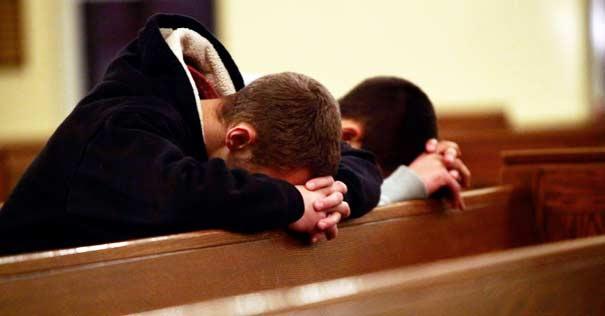 jovenes orando de rodillas en misa suplica