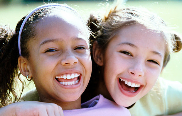 Two young girls smiling.