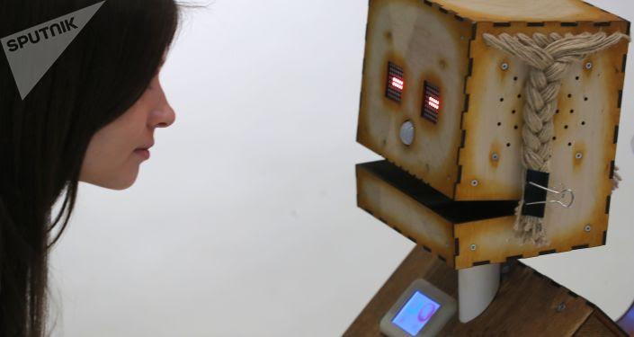 """Gość wystawy ogląda robota """"Derewiankę† firmy """"Robodem† na  forum """"SKOLKOVO ROBOTICS† w Moskwie"""
