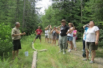 A man in DNR short and shorts talks to a group of male and female conference attendees in the woods