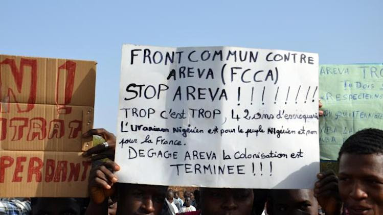 A protester holds an anti-Areva banner at a demonstration in Niamey on December 21, 2013